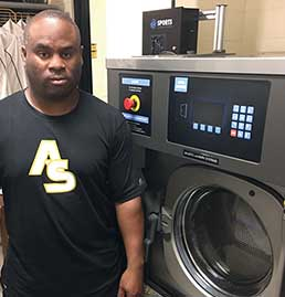 Alabama State University Equipment Manager standing next to a Sports laundry Systems Washer-extractor